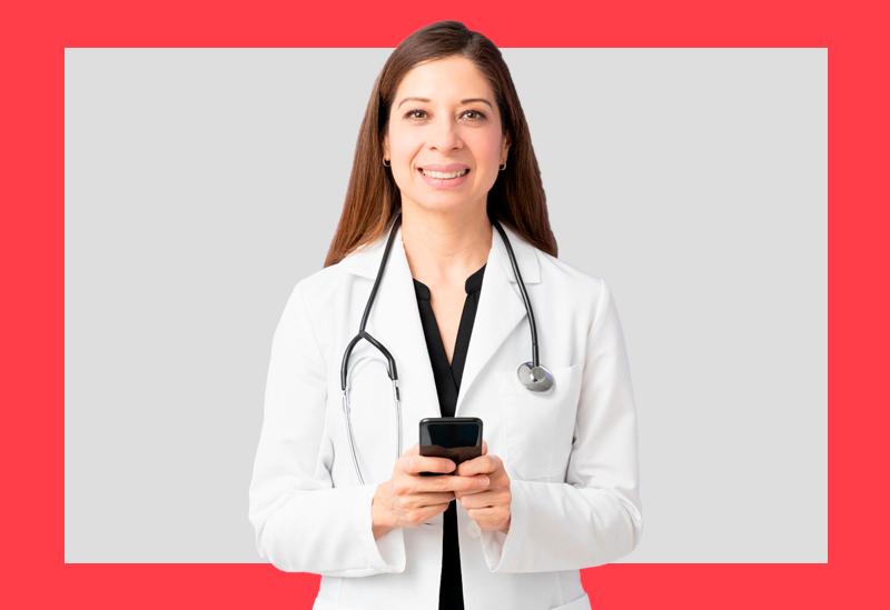 mulher de jaleco branco e aparelho de ouvir batimentos cardíacos segurando um celular nas mãos e sorri para a câmera